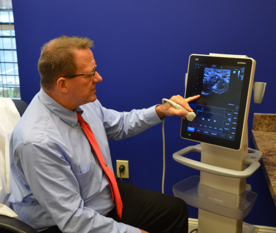Dr Altizer reading an ultrasound machine in the office