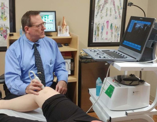 Dr. Altizer looking at a knee with an ultrasound machine